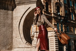 Outdoor fashion portrait of elegant, luxury woman wearing trendy leather  dark red skirt, beret, snakeskin print blouse, sunglasses, holding brown bag, walking in street of European city. Copy space