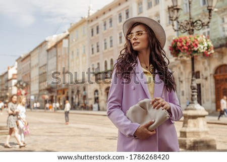 Outdoor fashion portrait of elegant woman wearing lilac suit, white hat, yellow sunglasses, holding trendy handbag, walking in street of European city. Copy, empty space for text Foto stock ©