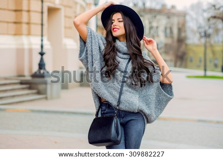Outdoor fashion portrait of glamour sensual young stylish lady wearing trendy fall outfit , black hat , grey sweater and leather bag. Cold season.Red lips. Warm  clothes.