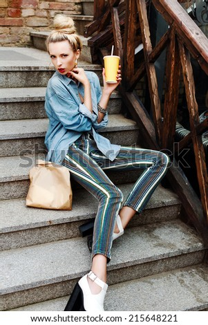 Outdoor fashion portrait of pretty young blonde sensual woman with drink glass and some food in paper pack have dinner on the street sitting on stairs