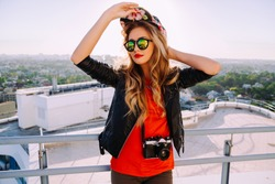 Outdoor fashion portrait of stylish photographer girl holding vintage retro camera, wearing bright swag hat, trendy sunglasses and leather jacket, amazing view of city from the roof.