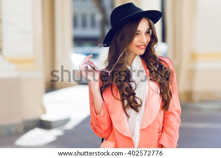 Outdoor  fashion portrait of stylish  pretty brunette  woman in night spring casual outfit walking in the city. Wearing white blouse, pink jacket, black wool hat. Long wavy hairstyle.