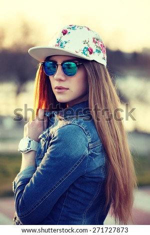 Outdoor fashion portrait of stylish swag girl, wearing swag cap, trendy  sunglasses and denim