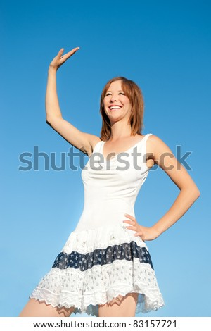 Outdoor fashion portrait of waving young woman wearing white summer dress under deep blue sky