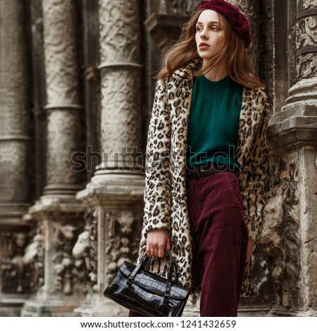 Outdoor fashion portrait of woman wearing trendy animal, leopard print faux fur coat, beret, sweater, corduroy trousers, holding  reptile skin textured bag, posing in street of city. Copy, empty space