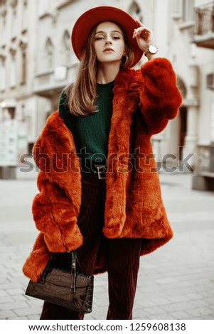 Outdoor fashion portrait of young beautiful confident woman wearing trendy orange faux fur coat, hat, green sweater, corduroy trousers, holding stylish handbag, posing in street of european city
