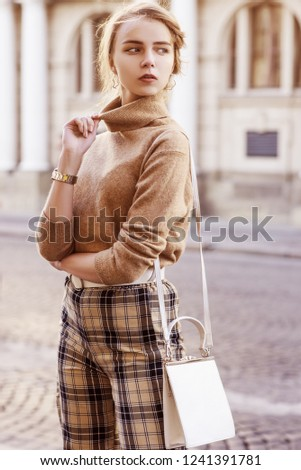 Outdoor fashion portrait of young beautiful fashionable girl wearing trendy beige cashmere turtleneck, high-waisted checkered trousers, belt, wrist watch, carrying small white bag, posing in street