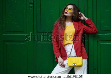 Outdoor fashion portrait of young beautiful woman wearing blazer, yellow sunglasses, blouse, white trousers, holding small quilted bag, posing near the green door. copy, empty space for text