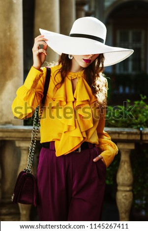 Outdoor fashion portrait of young beautiful woman wearing stylish white wide-brimmed hat, hiding her face, yellow blouse with frills, violet trousers, posing in street, near old european architecture