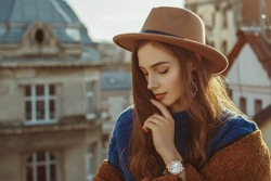 Outdoor fashion portrait of young elegant fashionable brunette woman, model wearing stylish hat, wrist watch, brown faux fur coat, posing at sunset, in European city. Copy empty space for text