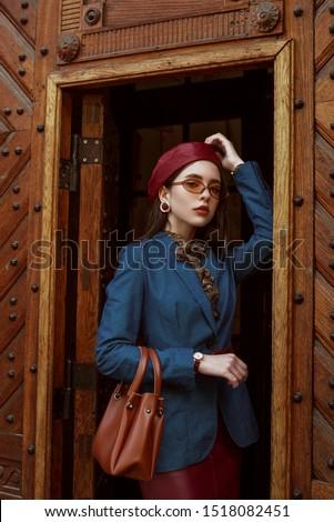 Outdoor fashion portrait of young elegant, luxury woman wearing red faux leather beret, skirt, wrist watch, blue denim blazer, beige glasses, holding brown handbag, posing in street of European city