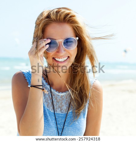 Outdoor fashion portrait summer beach style of young beautiful blonde woman fresh face smiling on the beach of tropic island having fun on vacation in blue dress and sunglasses