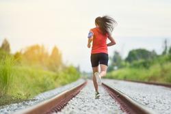 Outdoor fitness woman runner running on road. Sport athlete running woman runner jogging outdoor training for marathon race run. Young woman running