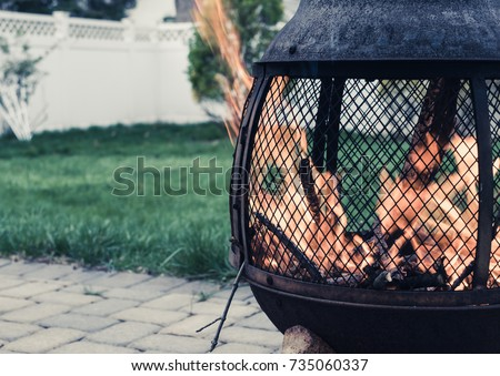 Outdoor flame pit with roaring fire. Chimera in backyard with strong fire and flames. Backyard with fire pit and white fence and lattice . Outdoor backyard paver with fire pit, green grass.