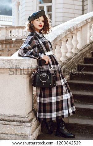 Outdoor full body fashion portrait of young beautiful fashionable girl wearing autumn long checked dress, leather beret, boots, holding black bag, posing in european city, near old architecture
