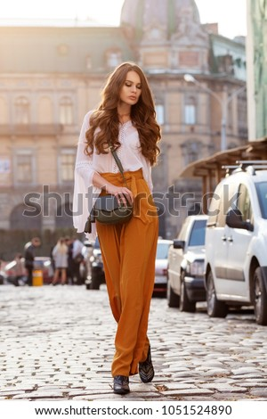 Outdoor full body fashion portrait of young beautiful woman wearing stylish yellow high-waisted wide-leg pants, white blouse, holding green leather bag. Model walking in street of european city #1051524890