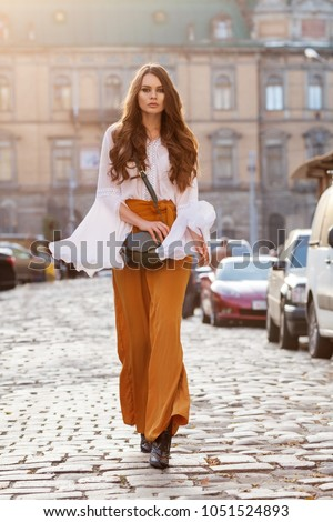 Outdoor full body fashion portrait of young beautiful woman wearing stylish yellow high-waisted wide-leg pants, white blouse, holding green leather bag. Model walking in street of european city