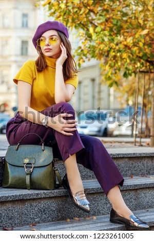 Outdoor full body fashion portrait of young elegant woman wearing purple beret, trousers, yellow glasses, turtleneck, loafers, wrist watch, with green leather handbag. Autumn street style concept