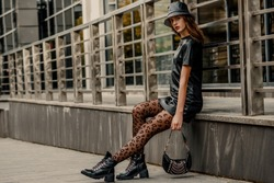 Outdoor full body street fashion portrait of young elegant woman wearing trendy leather bucket hat, dress, black leopard print tights, lace up ankle boots, holding small handbag. Copy, empty space
