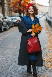 Outdoor full-length autumn portrait of young happy smiling fashionable lady wearing red beret, classic grey coat, tartan dress, holding leather bag, colorful fallen leaves, posing in street of city