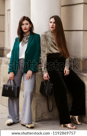 cd7d85d7 Outdoor full-length fashion portrait of two young beautiful women wearing  trendy clothes, shoes