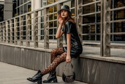Outdoor full-length fashion portrait of young elegant confident model, woman wearing trendy leather bucket hat, dress, black leopard print tights, lace up ankle boots, holding small bag. Copy space