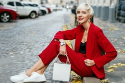 Outdoor full-length street fashion portrait of young smiling woman wearing total red look, suit: blazer, trousers; white sneakers, holding leather small bag. Model posing in European city. Autumn
