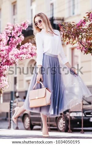 Outdoor fullbody portrait of young beautiful fashionable girl walking in street of european city. Model wearing stylish short dress, sunglasses, holding pink handbag. Spring, summer fashion concept