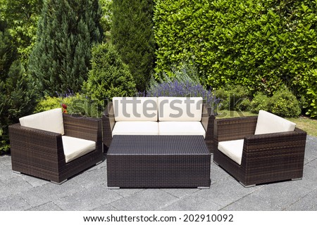 Outdoor furniture in green garden with with chairs, sofa and table in a patio.