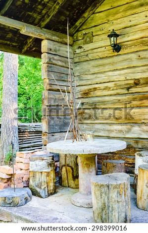 Outdoor furniture made of cut timber, concrete and other materials. Furniture is placed on a porch outside a cabin in the woods. Cabin is timbered with unpainted logs. Forest visible to the left.