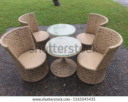 Outdoor furniture, rattan chairs and glass table on the terrace in the garden. #1165045435