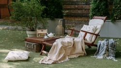 Outdoor garden wooden furniture at autumn nature, green grass. Nobody at home backyard with chair, lounge. Relax at outside terrace with blankets, pillows at retro, vintage decoration.