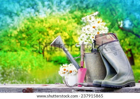 Outdoor gardening tools and flowers/ Spring Gardening tools and a straw hat on beautiful garden background