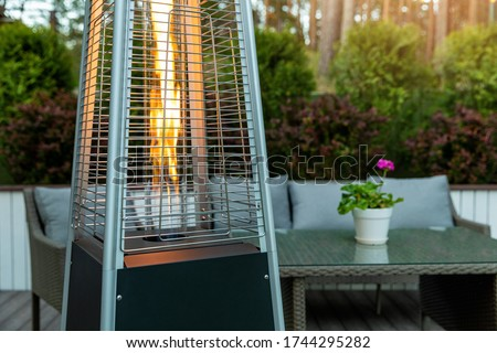 outdoor gas pyramid heater working on terrace Сток-фото ©