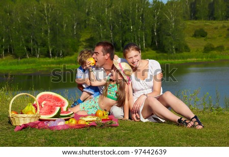 outdoor group portrait of happy family having picnic on green grass in park and enjoying fruits - stock photo