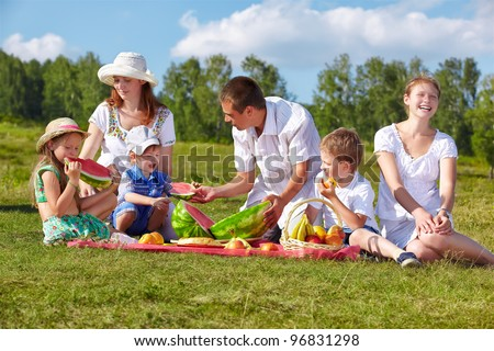 outdoor group portrait of happy family having picnic on green grass in park and enjoying watermelon