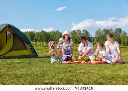 outdoor group portrait of happy family having picnic on green grass in park. father is cutting watermelon.
