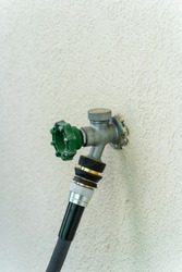 outdoor hose bib water connection on outside of stucco wall of house with quick connect and hose attached