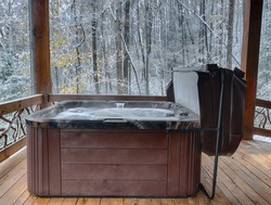 Outdoor hot tub on a cabin deck during winter snow