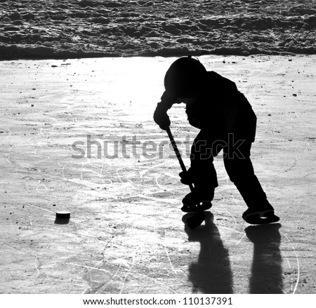 Outdoor ice hockey, silhouette of boy skating with puck and stick