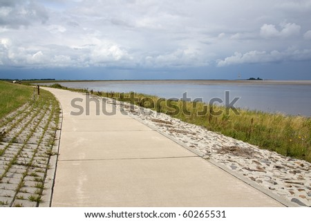 Outdoor image of a way at the dike along the river Weser at Blexen in the north of Germany.
