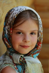 Outdoor image of beautiful smiley little girl wearing Pavloposadsky scarf over wooden background at summer