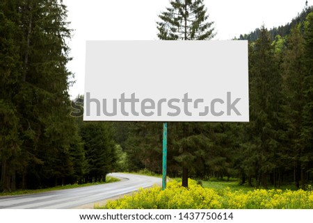 Outdoor image of blank huge billboard standing near road on way to mountains, having many evergreen trees around, sides of green divided by paved road, amazing landscape. Copyspace for advertisement.
