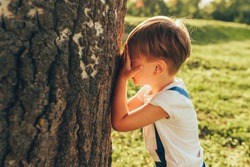 Outdoor image of cute little boy covering his eyes with hands, playing hide and seek standing next a big tree on sunlight and nature background. Adorable child having fun in the park. Childhood