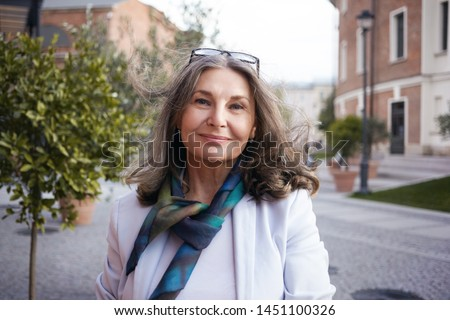 Outdoor image of gorgeous positive lady with charming smile and loose gray hair enjoying nice summer day, wearing white jacket, silk scarf and eyeglasses. Beauty, urban style and fashion concept