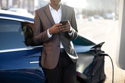 Outdoor image of of unrecognizable black man in formal business wear, leaning on his charging electric car and waiting for battery charge typing message on phone