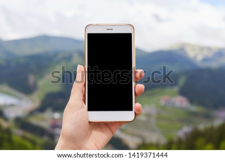 Outdoor image of one hand holding and showing white smartphone with blank black desktop screen with blur green mountains on background, mobile phone switched off. Copyspace for advertisement.