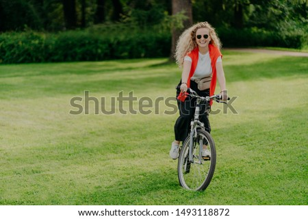 Outdoor image of pretty cheerful young woman rides bike, wears sunglasses, casual wear, poses on green lawn, spends free time in park, bikes in beautiful nature. Activity and recreation concept
