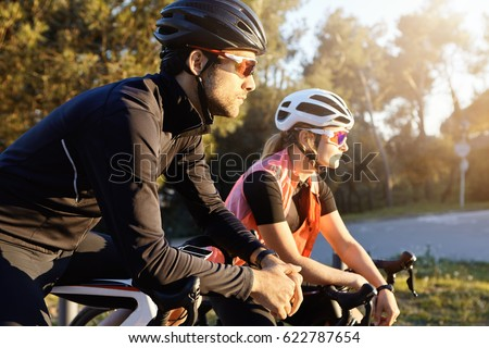 Photo of Outdoor image of sporty young European woman and man on bicycles during weekend cycle ride, stopped to admire nature in city park zone, standing in silence, listening to sounds of birds singing