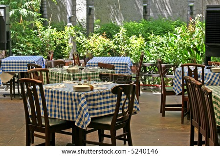Outdoor italian restaurant with chairs and tables with checked tablecloths